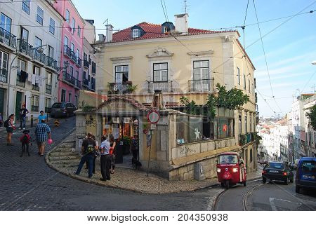 Lisbon, Portugal - October 19, 2014. Street view on Costa do Castelo in Lisbon, with historic buildings, city traffic and people.