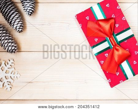Christmas theme with fir cones along with gift box on the wooden background. Top view. Holiday concept