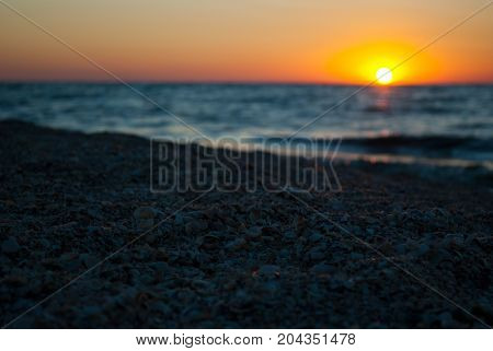 Beautiful sunrise over the sea, orange red sun, purple blue and pink sky without clouds, blue sea, sand wave vacation