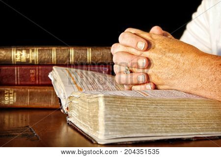 A woman clasps her hands in prayer on an open Holy Bible while other bibles are stacked nearby on the table.