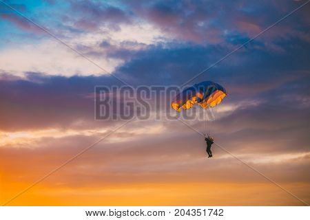 Skydiver On Colorful Parachute In Sunny Clear Sky At Sunset Or Sunrise Time. Active Hobbies