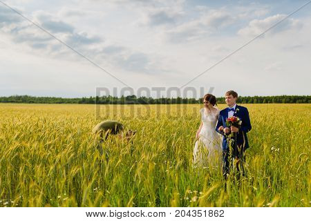 Photographer making pictures couple of newlyweds through the ears