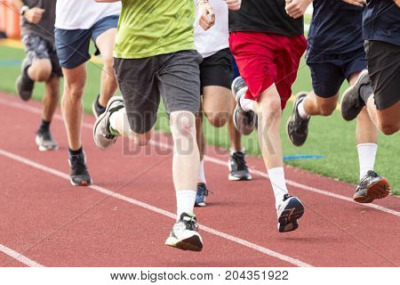 A group of high school boys running on a red track during practice after school.