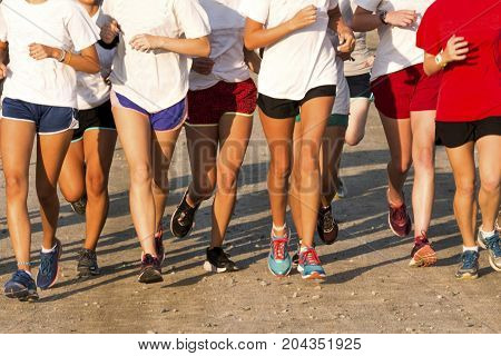 A group of high school girls running on a dirt path in the bright sunshine during cross country practice.