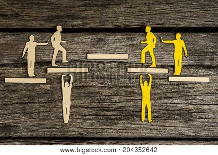 Small silhouette people on top of paper blocks pushing others of their own color up steps over dark wooden background.