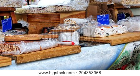 Market Stall Selling Hand Made Nougat On Traditional Wooden Boards, Flavored With