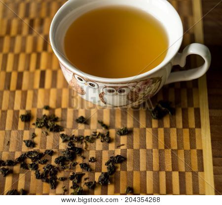 The cup of green tea on wooden table