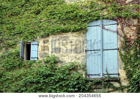One small and one large pair of pale blue wooden shutters on an on stone French house overgrown with ivy