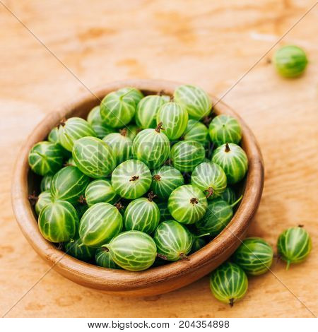 Old Wooden Bowl Filled With Succulent Juicy Fresh Ripe Green Gooseberries On An Old Wooden Table Top.