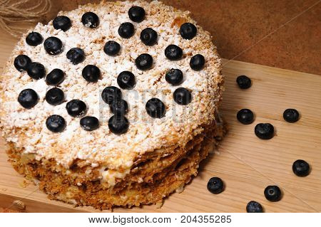 layer cake Napoleon with berries blueberry on a rough wooden tray, sprinkle with powdered sugar background for menu cafe or pastry shop