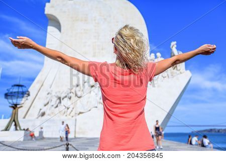Happy tourist woman with open arms in front of Discoveries Monument on blurred background. Female caucasian enjoying at popular landmark in Belem District, Lisbon, Portugal. Europe travel concept.