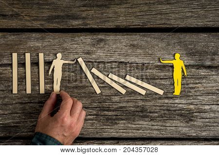 Man Carefully Positioning Small Wooden Figure
