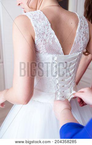 bridesmaid helps the bride to wear wedding dress