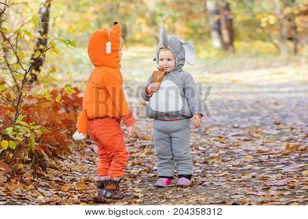 Little children in animal costumes boy dressed as fox girl as elephant playing in autumn forest