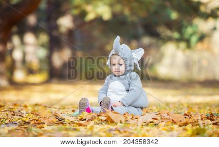 Cute little girl in elephant costume playing in autumn forest