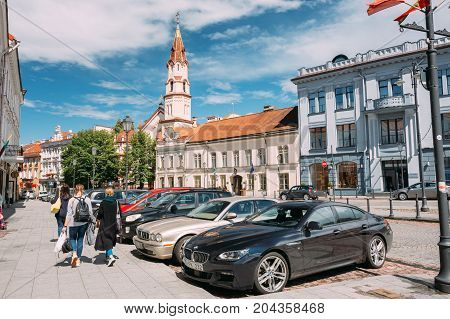 Vilnius, Lithuania - July 5, 2016: Young Women People Walking In Rotuses Street In Old Town. Parked Luxury Cars And St. Nicholas Church In Sunny Summer Day.