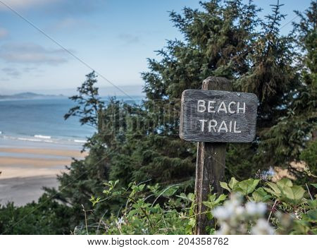 Beach Trail Sign Above Pacific Ocean with beach in background