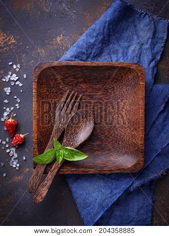 Empty wooden plate, cutlery, salt, pepper and basil. Culinary background Top view