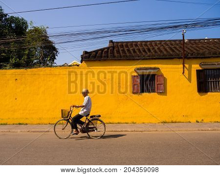 Hoian, Vietnam - August 05, 2017: Unidentified man biking in front of an old yellow house in Hoi An ancient town, UNESCO world heritage. Hoi An is one of the most popular destinations in Vietnam.