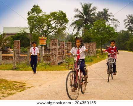 Hoian, Vietnam - August 05, 2017: Unidentified children biking in a road, back to home in Hoi An ancient town, UNESCO world heritage. Hoi An is one of the most popular destinations in Vietnam.
