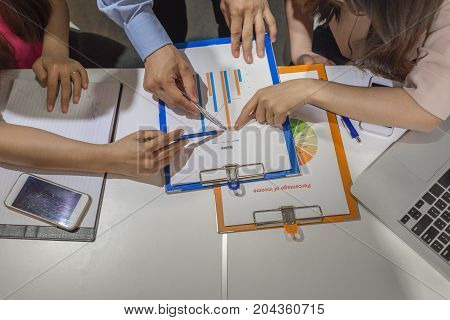Three business people point at the chart at the same time