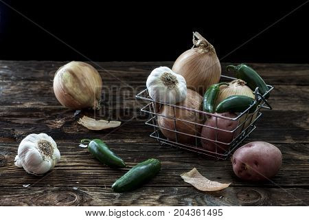 Assorted veggies in a basket. A still life photo of assorted veggies such as garlic potatoes peppers and onions.