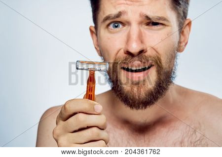 Man with a beard on a light background holds a razor, portrait, emotions.
