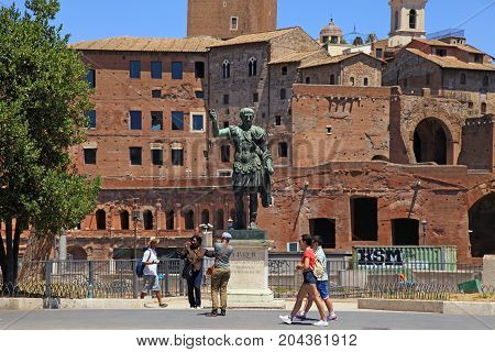 ROME, ITALY - JULY 17, 2017: Tourists and bronze statue of Emperor Trajan on Via dei Fori Imperiali near Roman Forum, Rome, Italy.