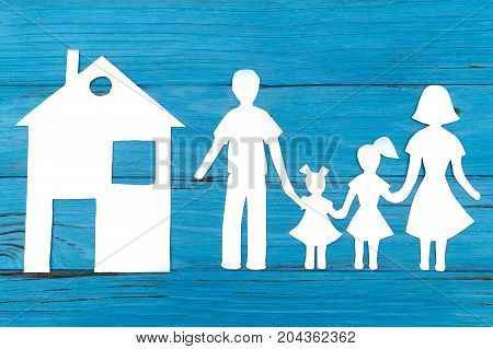 Closeup of happy paper family on blue background. Social protection concept