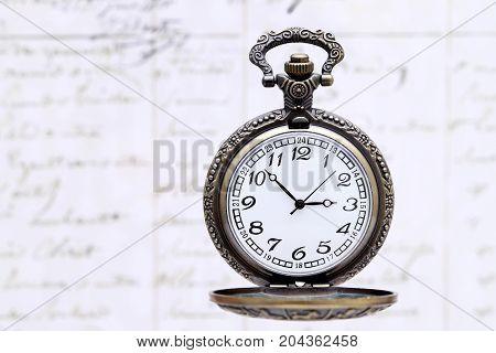 antique pocket watch on old letter background