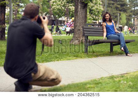 Boy taking a photo of a girlfriend in park