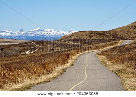 Rural prairie scene with winding pathway and mountain background
