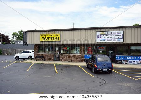 JOLIET, ILLINOIS / UNITED STATES - JULY 21, 2017: One may have one's skin tattooed at Wolf's Fine Line Tattoo, and have one's computer repaired at the Computer and Phone Repair Center, in the Pine Tree Plaza on Plainfield Road.