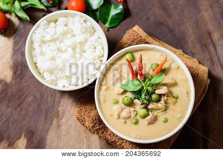 Thai food (Phanaeng curry), red curry with pork and cooked rice in a bowl on wooden background