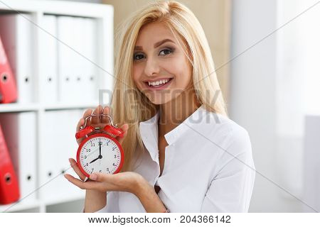 Smiling Business Woman Holding In Hand On The Alarm Clock