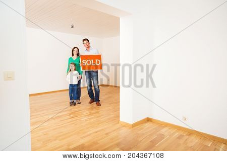 family in an empty apartment, holding 'sold' sign