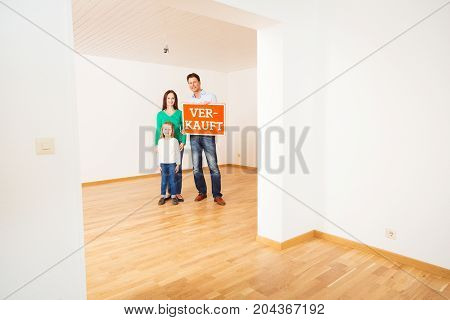 family in an empty apartment, holding 'verkauft' sold sign
