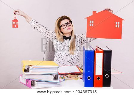 Thinking business woman sitting working at desk full off documents in binders she having big red house made of paper real estate concept.
