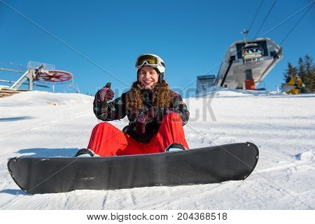 Happy Snowboarder Girl Sitting In The Snow Near A Ski Lift Against A Blue Sky And Showing Thumbs Up