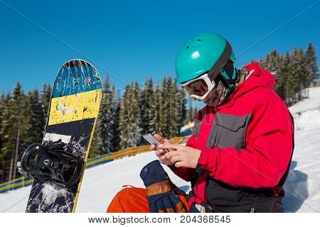 Close-up portrait of male snowboarder sitting in the snow using his smart phone while resting in the mountains technology communication carrier mobility recreation sport lifestyle