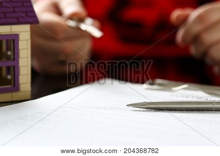 Silver Pen Lie On Paper Form With Man Hold In Arm Key