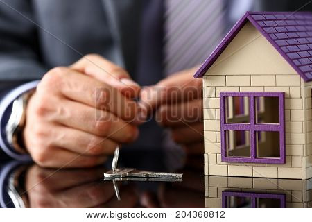 Man In Suit And Tie And Silver Key And Little Toy House