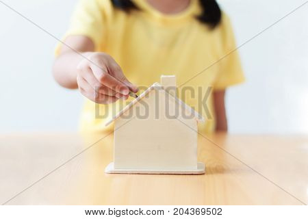 Close up shot hand of asian little girl putting money coin into house piggy bank shallow depth of filed concept saving money for house and real estate