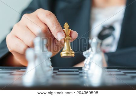 Close up shot hand of business woman holding golden chess between row of silver chess on white and black chess board for business challenge competition winner and loser concept select focus