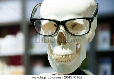 Skull head wearing eyeglasses and white scientific lab coat. Educational material for display against blurred background