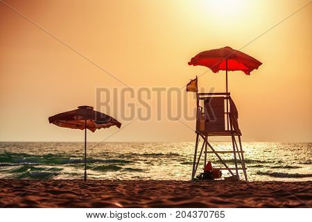 Sunrise with life guard station silhouette on the beach