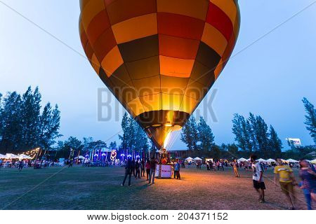 Chiang Mai Thailand - 04 March 2016 - Hot air balloon stays on the field with people walking around at Chiang Mai Balloon Festival on an evening of March 04 2016 in Chiang Mai Thailand.