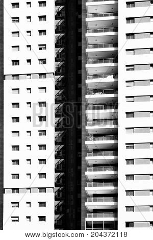 Facade of dwelling house with harmonic windows in a row. Windows and balconies of a multiroom apartment house of mass building in Israel. Black and white picture