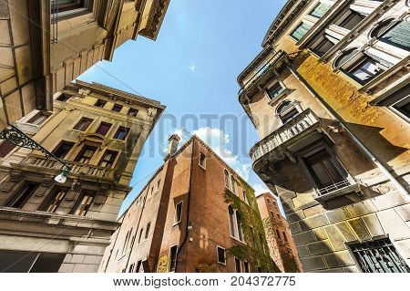 Architecture of medieval Venice. Houses peeling off from dampness.