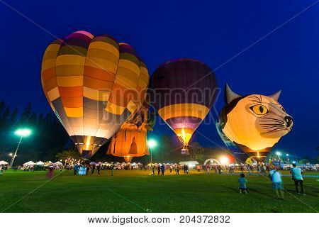 Chiang Mai Thailand - 04 March 2016 - Hot air balloons light up on the field against blue evening sky with people walking around at Chiang Mai Balloon Festival on March 04 2016 in Chiang Mai Thailand.